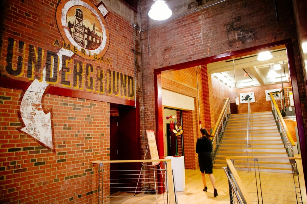 Main hallway at American Underground logo on the old brick walls.