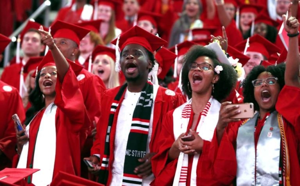 NC State students in red graduation attire in mid-celebration! They are cheering and yelling in a crowd.
