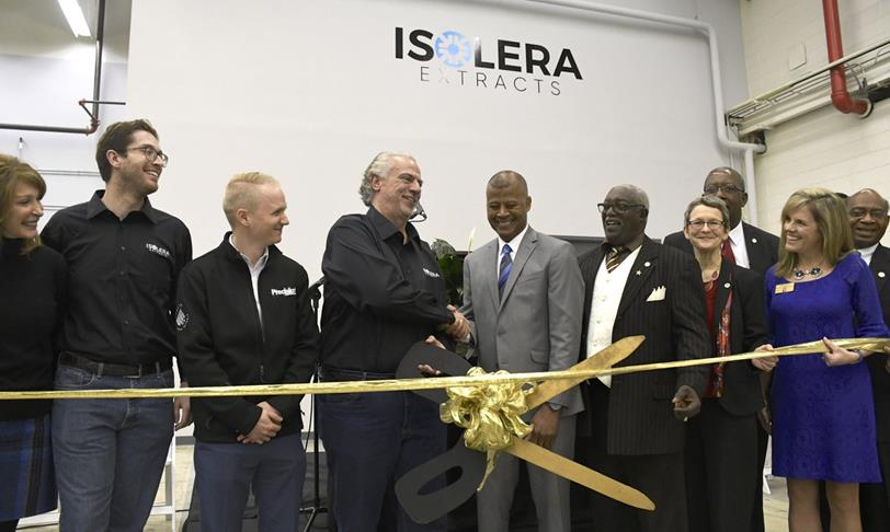 Isolera grand opening with leadership performing the ribbon cutting ceremony. Two men are shaking hands and holding a large pair of scissors.