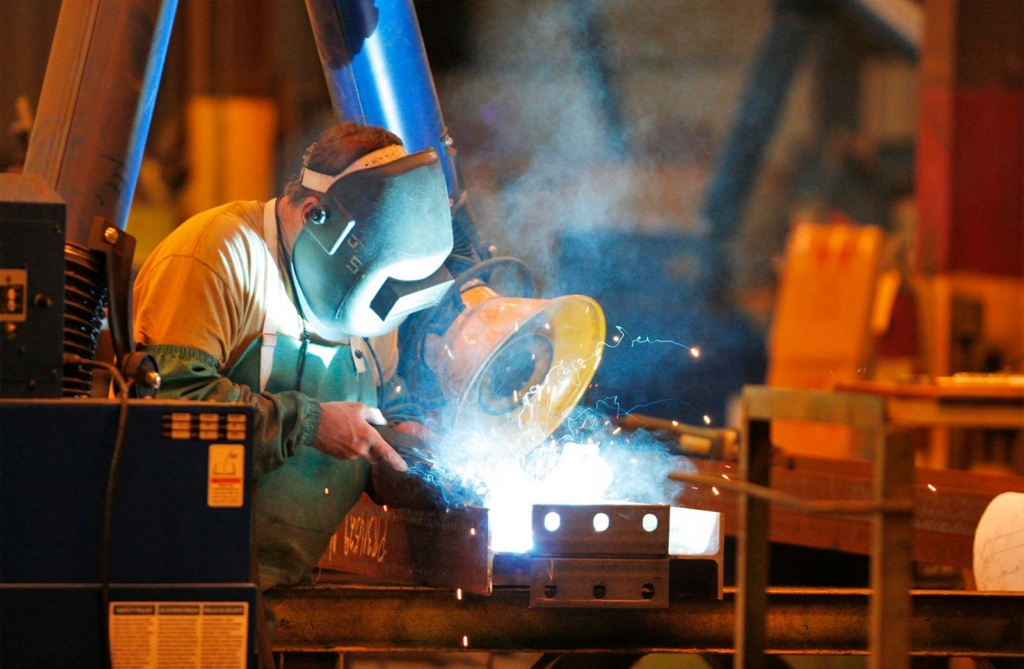 A person wearing protective headgear while working on metal with welding gear.