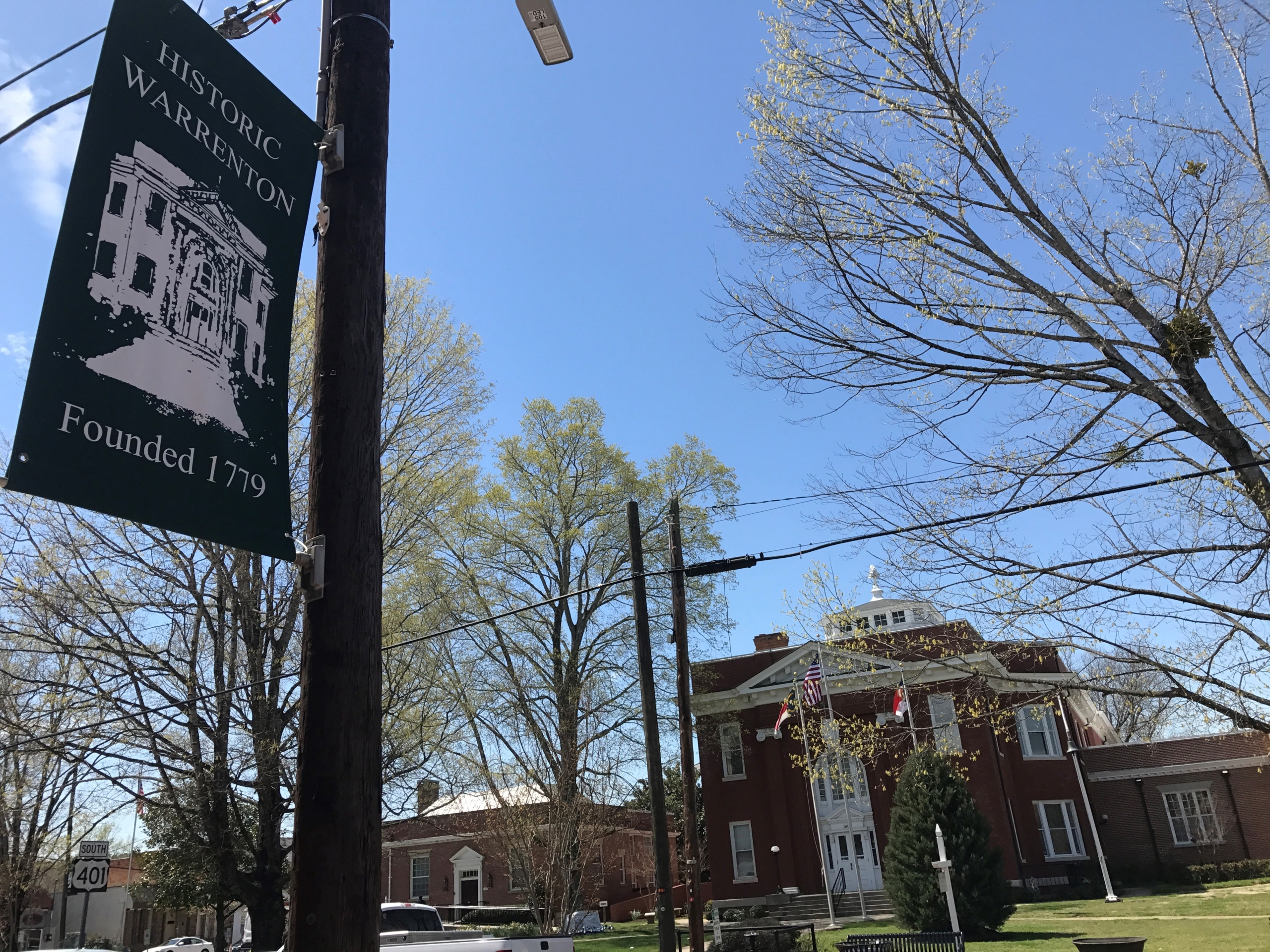 A lightpole with a banner containing the Historical Warrenton logo. The banner states the town was founded in 1779.