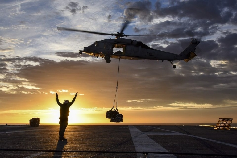Military helicopter airlifting a supply drop with a crew member directing from the ground.