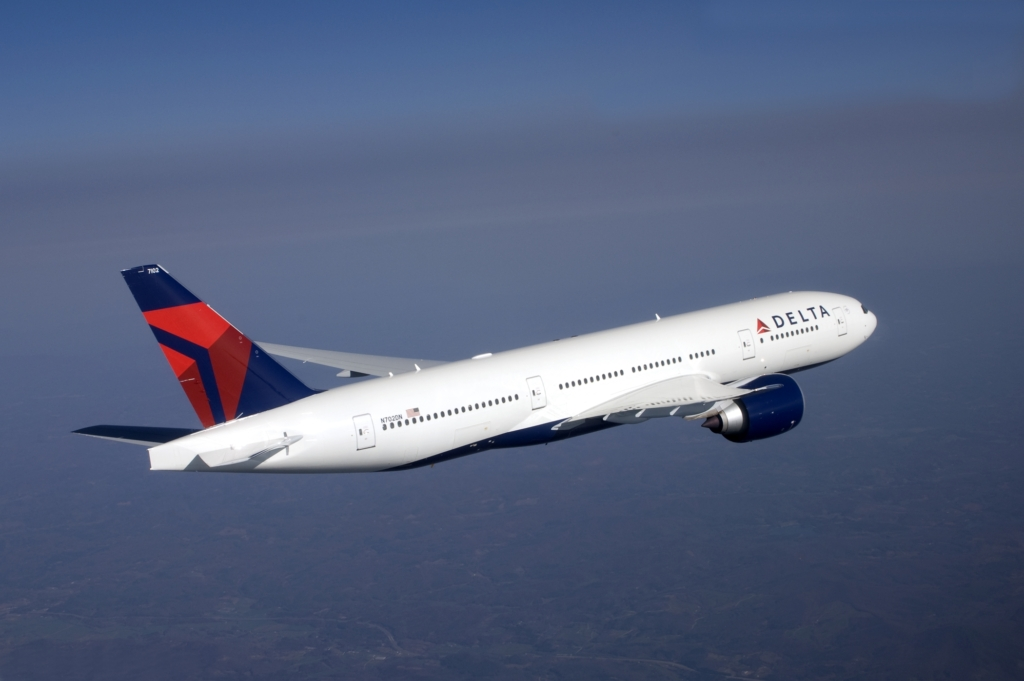 A zoomed in image of a Delta airliner mid-flight at high altitude.