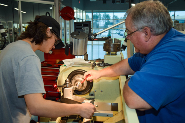 Manufacturing and technology students working carefully with a lathe machine in a workshop.