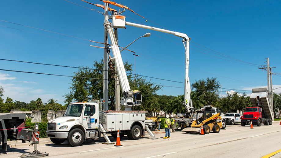 A PowerSecure utility truck on the side of the road repairing a telephone pole. The truck's arm is extended up to the top of the pole with workers below.
