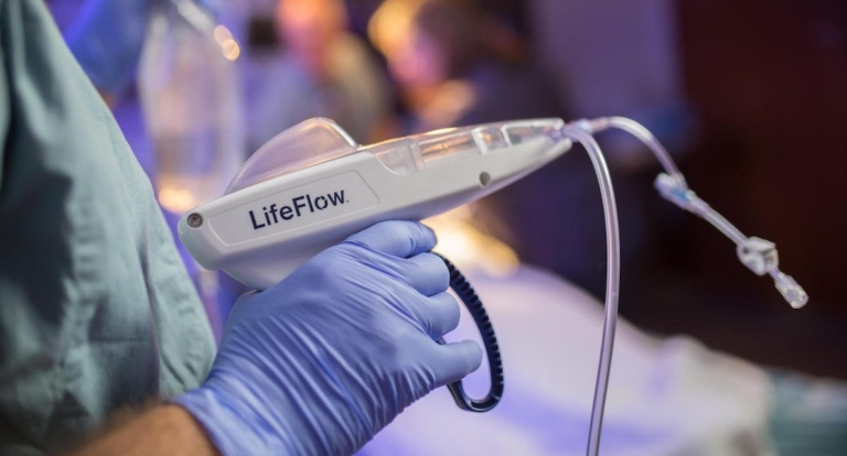A pair of medical gloved hands holding a LifeFlow device.