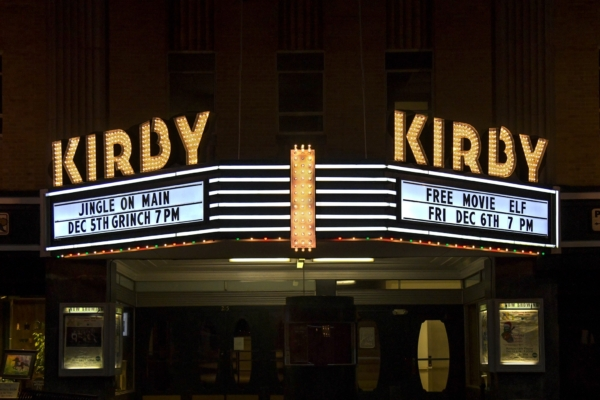 The Kirby Theatre marquee lights on at night.