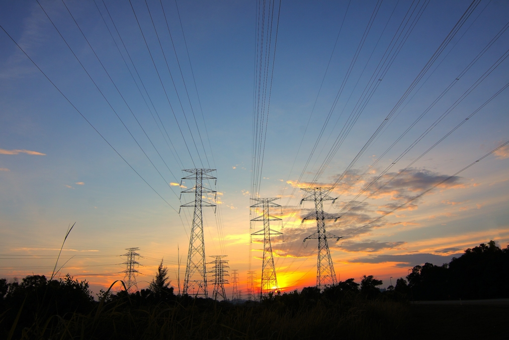 Electrical utility towers silhouetted by a golden sunset and a few wispy clouds.