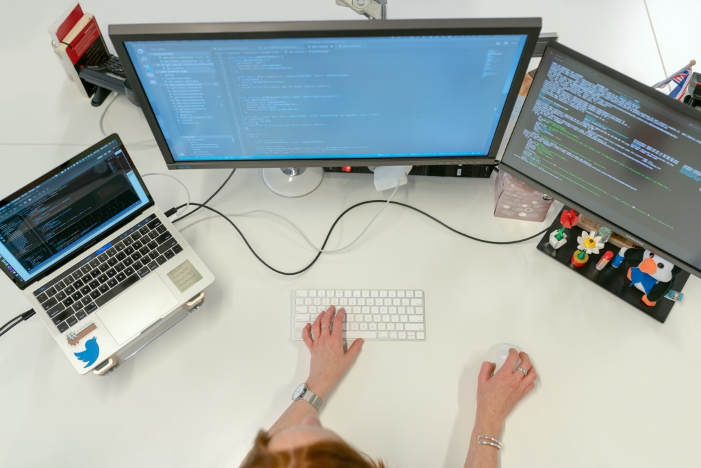 Overhead view of a person sitting at a desk with a laptop and two monitors.