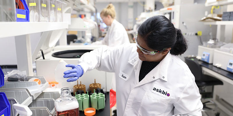 An AskBio lab professional pouring a liquid solution into a container.