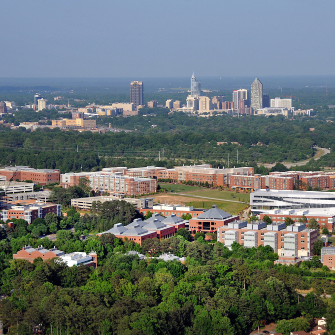 Aerial view of Centennial Campus, with the campus in the foreground, and downtown Raleigh in the distant background.