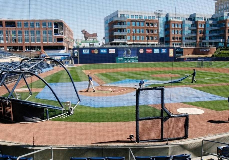 Durham Bulls stadium on a sunny afternoon. Crew members are removing rain tarps from the field.
