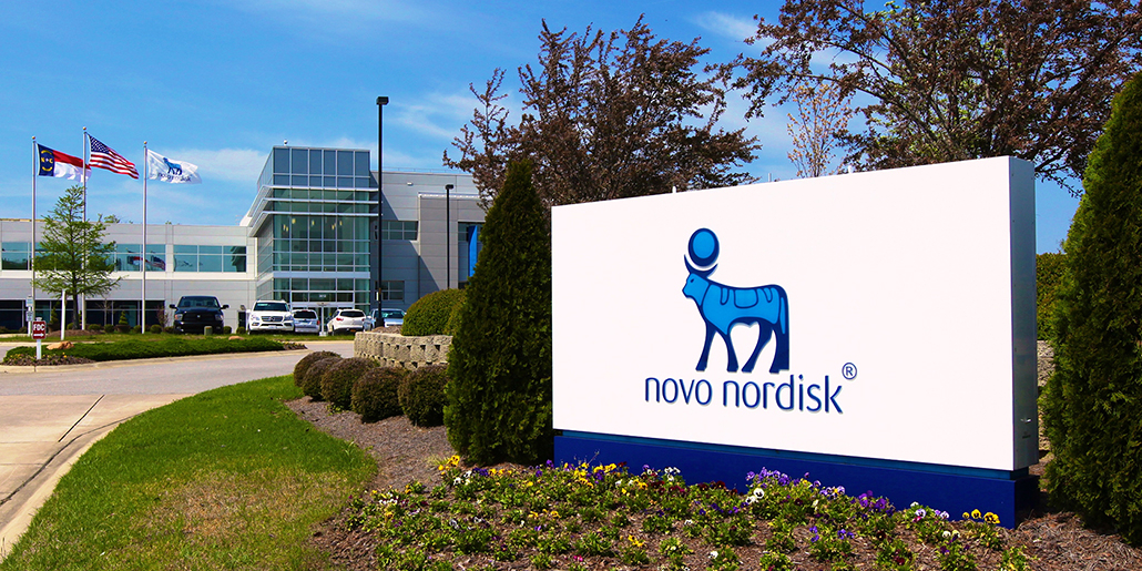 Front entrance of NovoNordisk facility. The company logo is on a white sign with the main building right behind it.