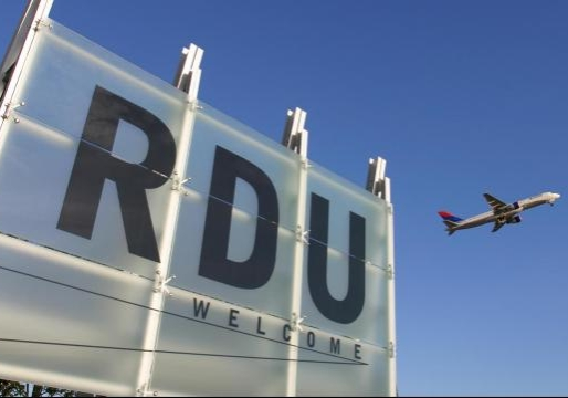 Front sign of RDU airport. An airplane is taking off in the background.