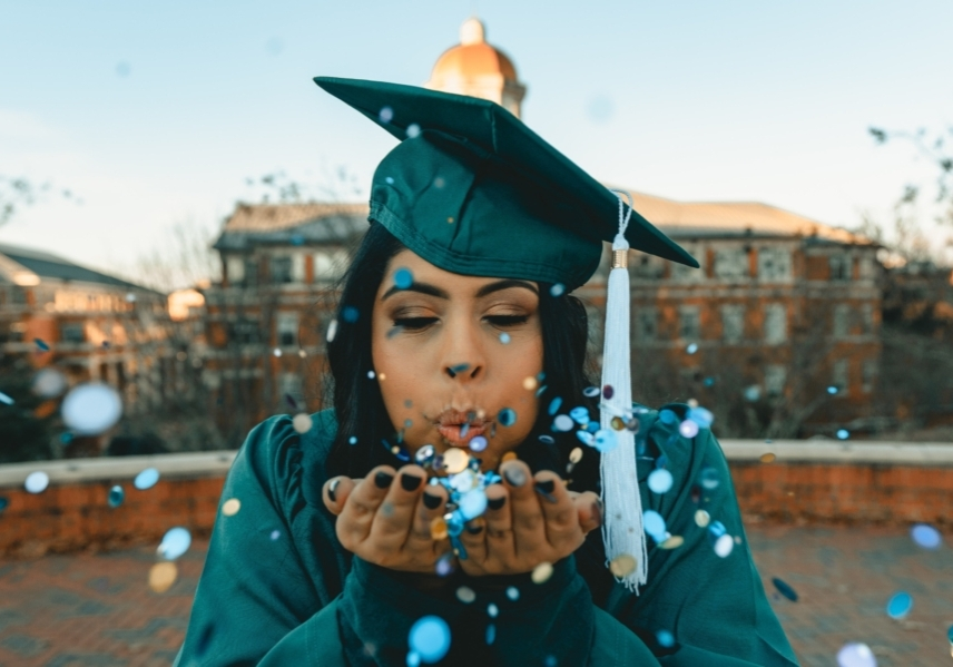 A young graduate in cap in gown. She is blowing confetti towards the camera from her outstretched hands.