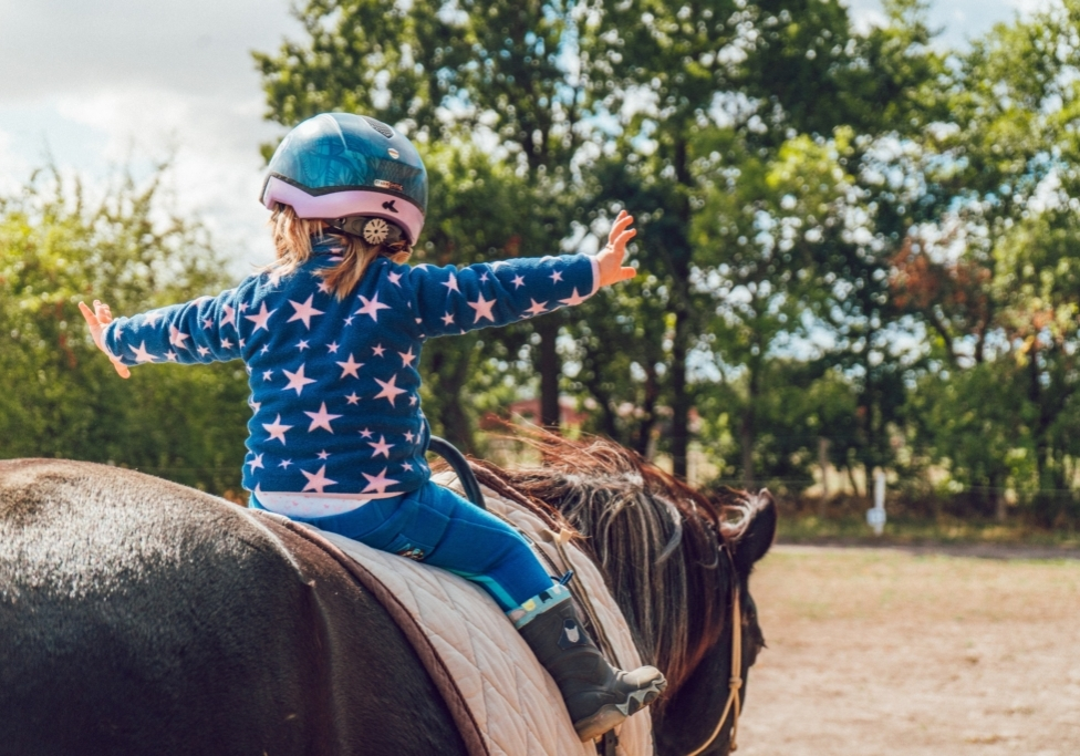 Young girl riding a horse and holding her hands out. The girl is wearing a distinctive blue outfit with moon and star patterns.