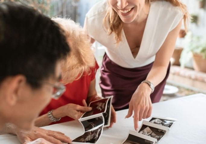 A group of three reviewing images from a sonogram in excitement!