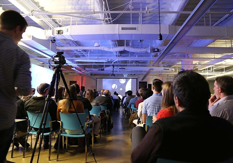A large presentation with a seated crowd and a speaker distant at the front of the room. A videographer is quietly recording the presentation with a handheld video camera on a tripod.