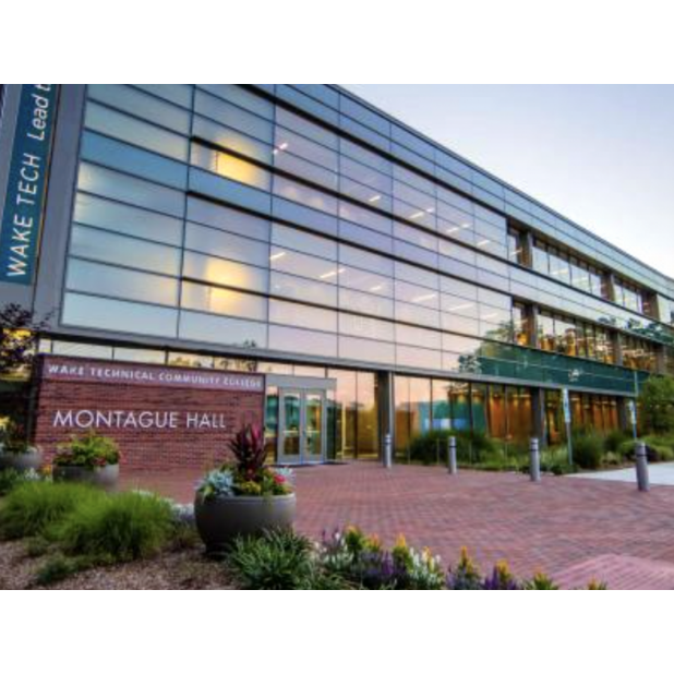 Front of the Montague Hall at Wake Tech. The building's glass front is reflecting a sunset.