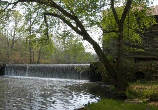 A water dam located in Warren County. Water is running over the dam into a calm pool below.